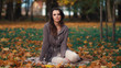 Beautiful woman relaxing in autumn park
