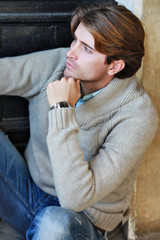 handsome young man sitting near door