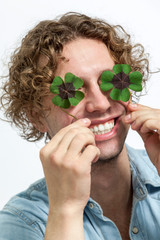 Smiling Young Men Covering her eyes with 4 leaf clover  - Stock