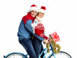 Happy couple on bicycle with christmas present.