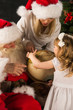 Santa Claus sitting at home with family - little girl and her mo