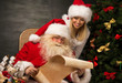 Portrait of happy Santa Claus with his helper reading Christmas