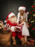 Photo of cute girl and her mother and Santa Claus holding giftbo