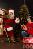 Santa Claus taking picture of cheerful man with old wooden camer