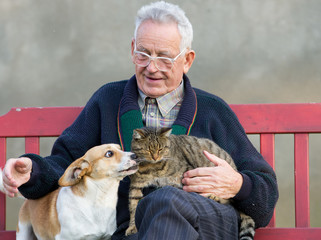 Senior man wirh dog and cat on his lap on bench