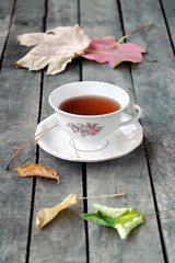 autumn tea in white vintage cup on rustic wooden table