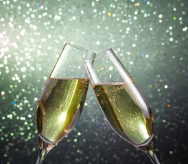 champagne flutes with gold bubbles on green light bokeh