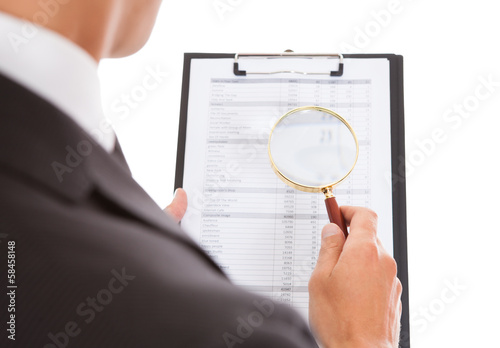Man Looking Through Magnifying Glass On Clipboard