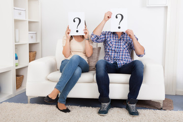 Couple Holding Question Mark Sign In Front Of Face