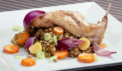Baked rabbit leg with lentil and vegetable garnish