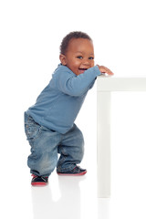 Beautiful african baby standig with a table