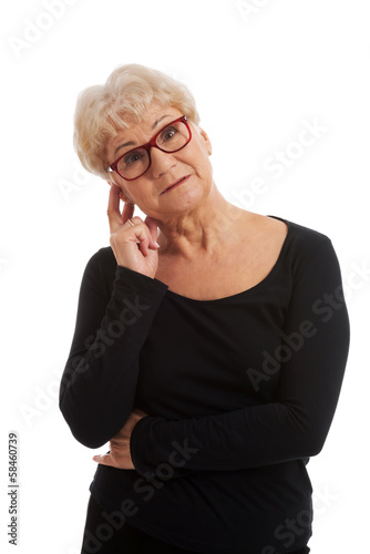 An old lady in eyeglasses touches her face.