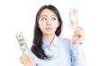 日本円と米ドルの紙幣を比べる女性