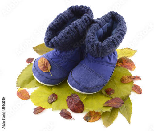 Kids blue high boots on heap of leaves