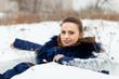 girl in coat  lying down on snow