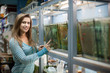 Woman chooses  fish  at pet-shop