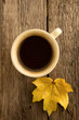 A cup of coffee on a background of maple leaves.