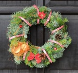 Christmas wreath with red ribbon and nut hanging on the door.