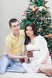 pregnant woman with the husband sit at a New Year tree