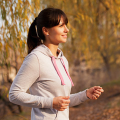 Happy middle-aged woman running at sunset.