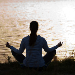 Silhouette of woman in meditative pose