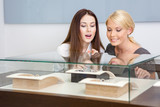 Two women looking at showcase with jewelry at jeweler's shop
