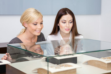 Two girls looking at showcase with jewelry at jeweler's shop