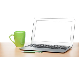 Laptop with blank screen and cup on table