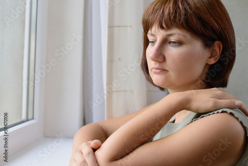 Sad young woman standing thinking