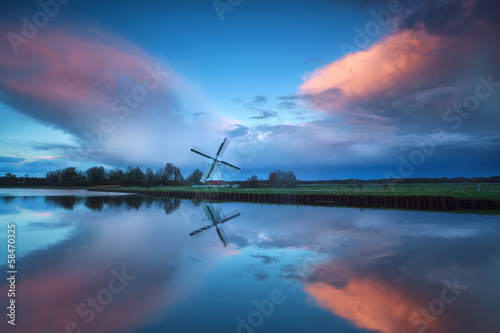 dramatic stormy sunset over Dutch windmill and river