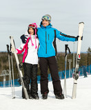 Full-length portrait of two embracing downhill skiers