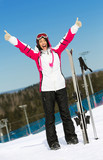 Full-length portrait of female skier with hands up