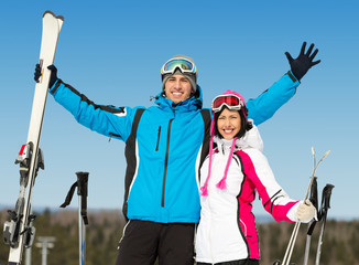 Half-length portrait of two hugging downhill skiers
