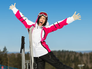 Half-length portrait of female skier with hands up