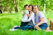 Family of three has picnic in park