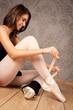 ballerina tying her ballet slippers