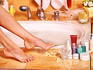 Woman wash leg in bathtube.