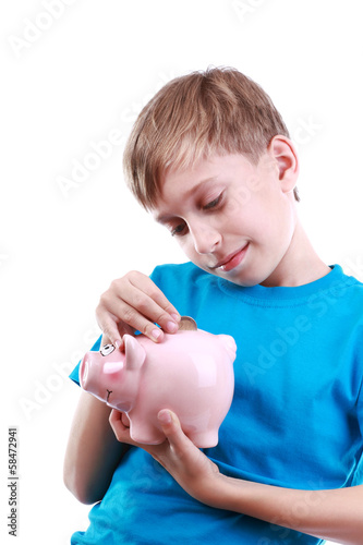 Beautiful cheerful blond child puts a coin into piggy bank