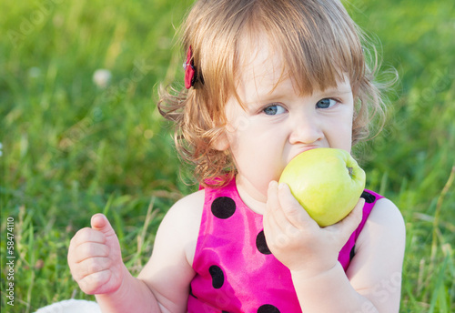 little girl is holding green apple