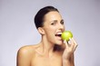 Lovely brunette woman eating fresh green apple