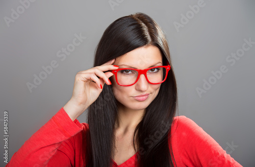 Girl looking over glasses, studio shot on gray background