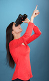Girl looking through the binoculars, blue background