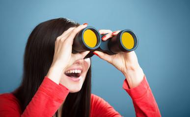 Playful girl looking through the binoculars, blue background