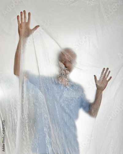 Silhouette of a man behind a transparent plastic