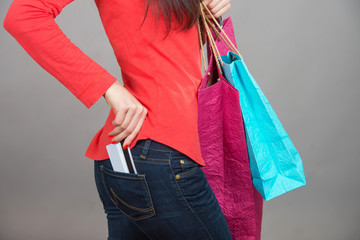 Credit card in pants pocket, female hand with shopping bags
