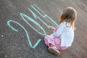Little girl writing 2014 on asphalt