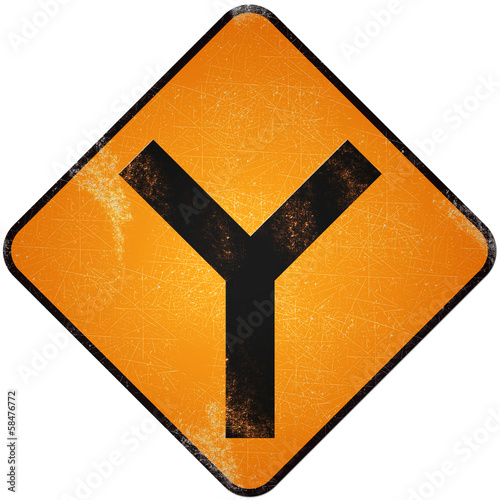 Fork road sign. Damaged yellow metallic road sign with fork symb