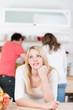 nachdenkliche junge frau in der küche mit freunden
