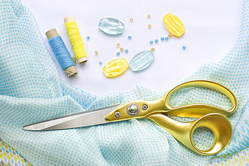 large scissors with gold handles are on the silk fabric