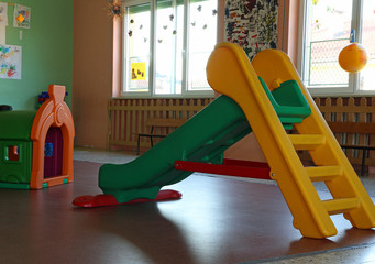 plastic chute green and yellow in the playroom inside the asylum